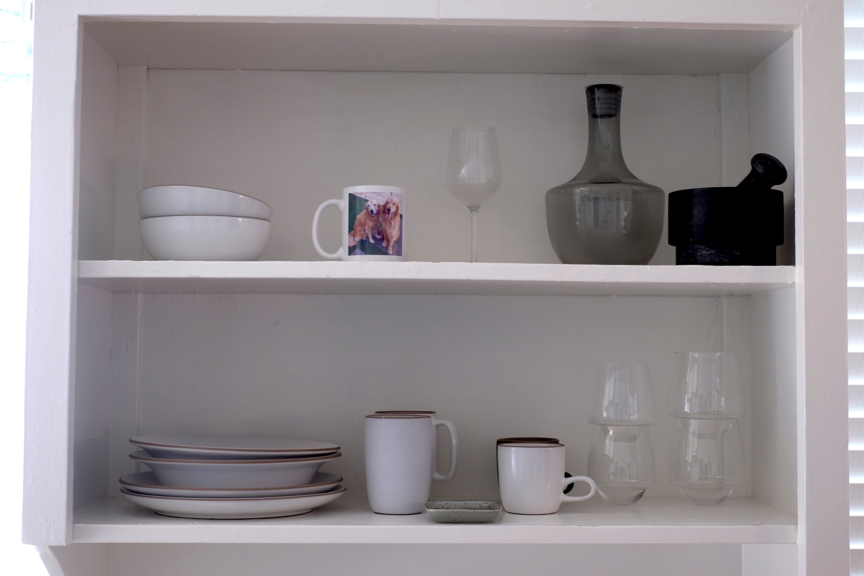 My tableware shelf: Heath plates and bowls, SDS Saturn Glasses (red wine and white wine), an Ikea wine glass I use as a tea light holder, a water pitcher (also Ikea), a mortar and pestle, a sauce dish given to me by my friend Benny, and a mug with a picture of my dogs