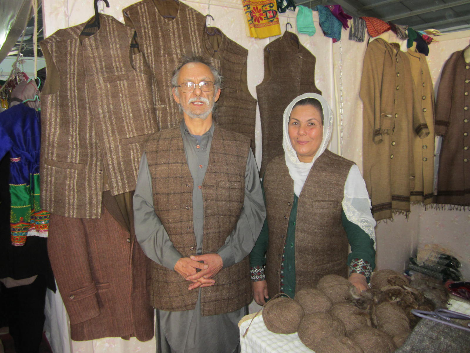 Zahra Kazemi at the trade fair in Kabul where she met Yosuf Taraki, a member of Growing Peace in Afghanistan, in October 2018. Vests made of barak are hanging in the background and Yosuf is wearing one.