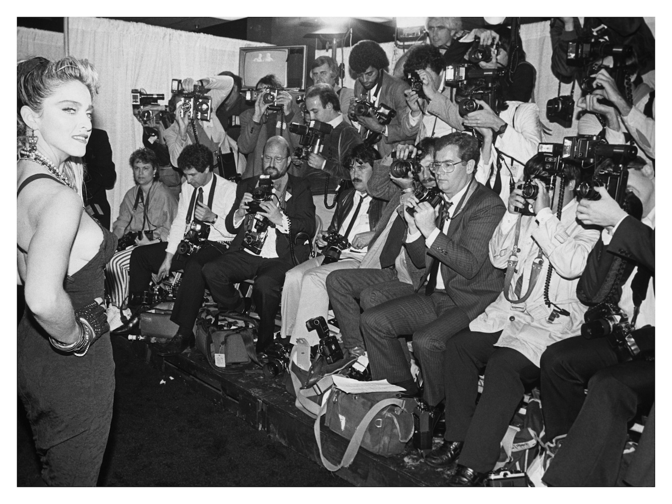 """Madonna Meets The Press, 1982 - Every year, I always hired by Dick Clark to photograph is American Music Awards. This gave to total access everywhere. While all the press were sequestered in the """"Bull Pen"""", I was free to make a creative photograph of this new singer Madonna. When the photo was published all over the world, the publicist expressed his displeasure. He did not care about works or art, all he cared about was DC Productions logo in every photo. Needless to say, every magazine run my Madonna photo. All over the world!"""