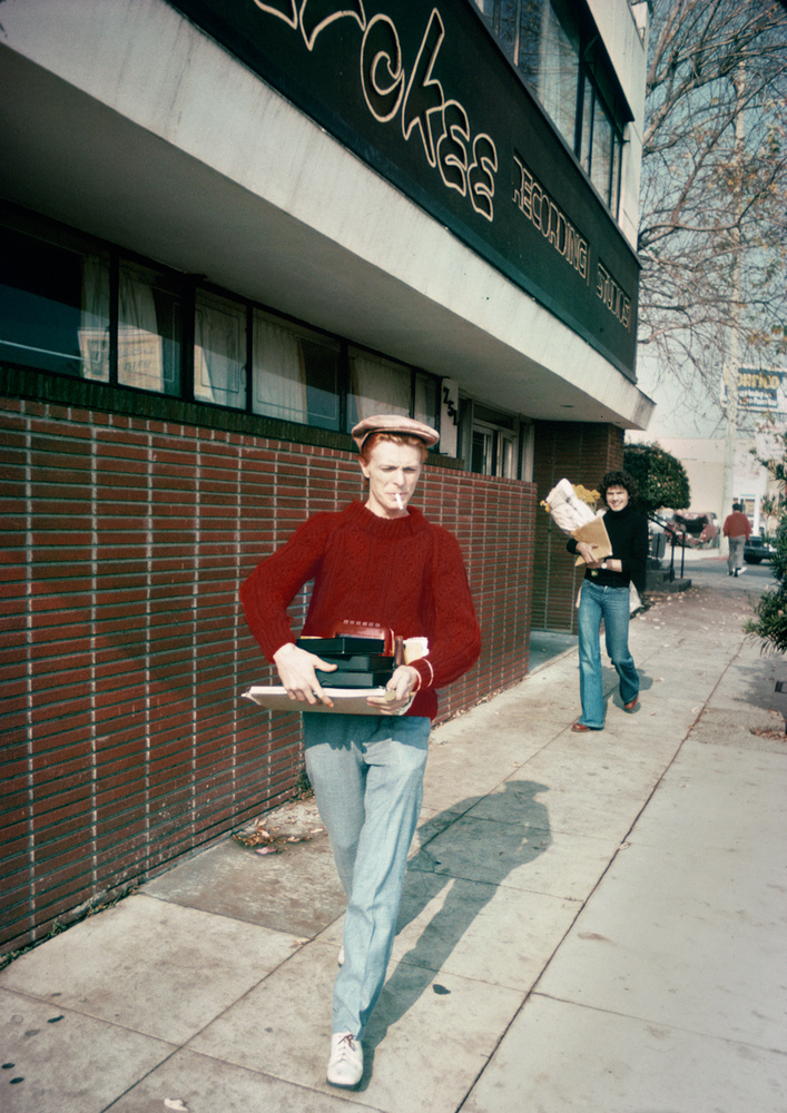 """David Bowie: This Photo Changed My Life, 1975 - I wanted to take a photo of David Bowie in the worst way. I called his publicist for a photo pass, but I was turned down.Bowie permitted only a handful of photographers to take his photo and teenage me was not one of them. . My friend Michelle Meyer told me that Bowie was having an all night recoding session at Cherokee on Fairfax and that he leaves around 6am every morning. What did I have to lose? I got there just before the sun came up and a few moments later he walked out the door looking so stylish and cool. The guy behind Bowie is the legendary record producer Paul Buckmaster. Bowie did not say much, except """" Good Morning"""". The whole event took place in about 22 seconds, but it seemed to go on forever and I knew that it was something special. The photo was published everywhere and the funny thing is that the local PR and record companies all embraced me for having the insight and balls to make the photo and was plastered all over the world. I was on my way!"""
