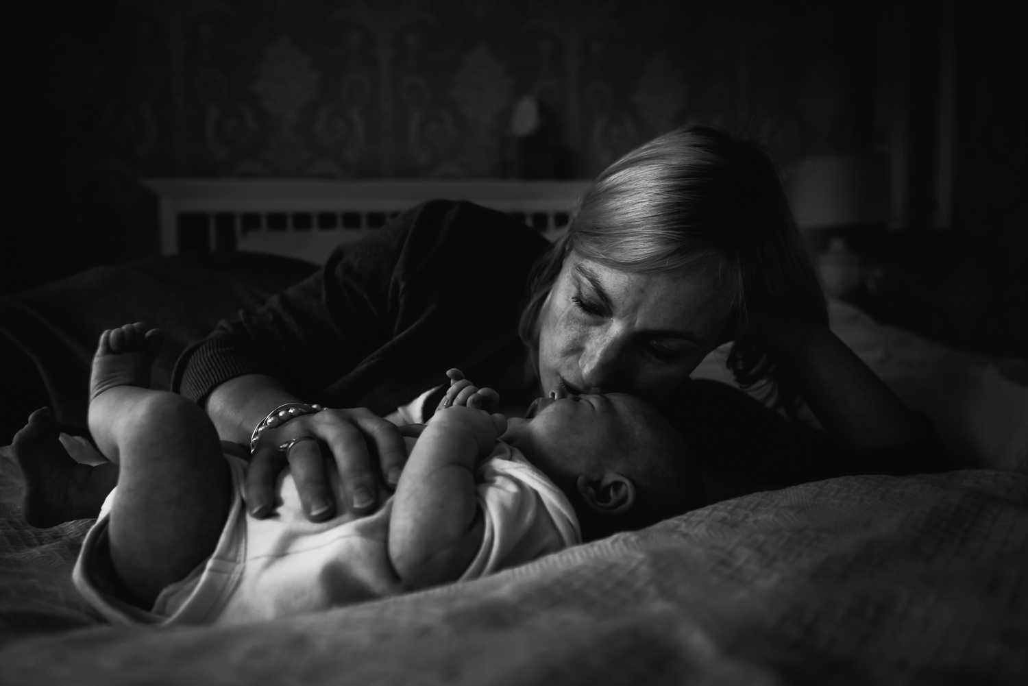 Mother comforts her newborn on a newborn shoot with Diana Hagues Photography