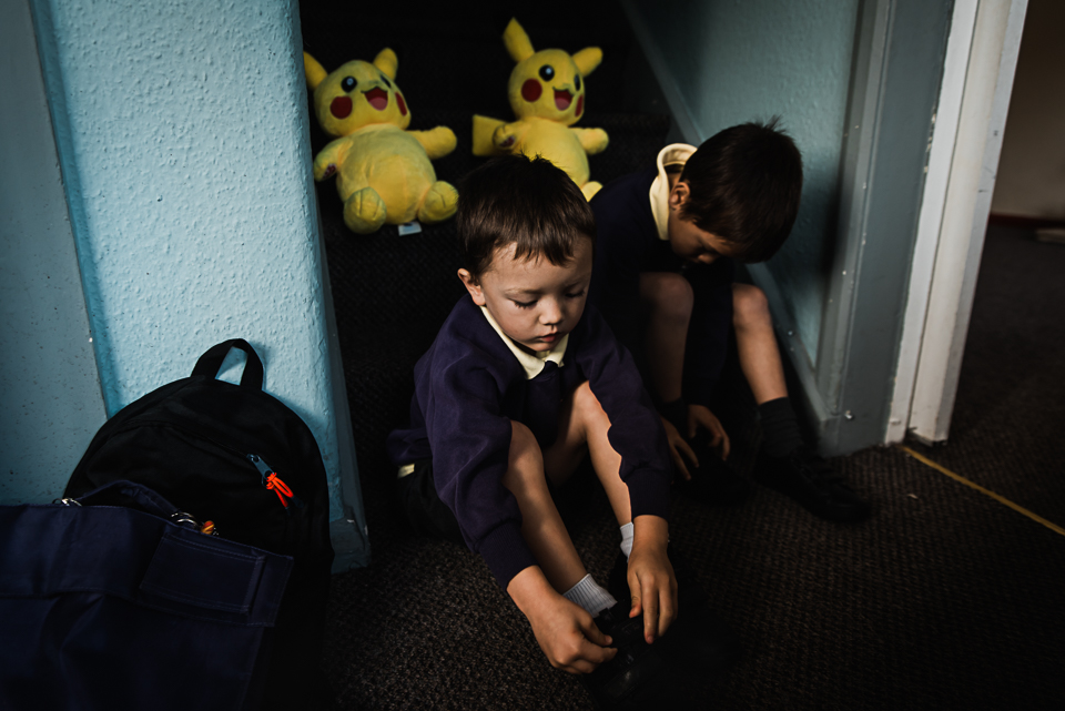 Pikachu toys watch on as boys put on shoes | morning routine in day-in-the-life photography