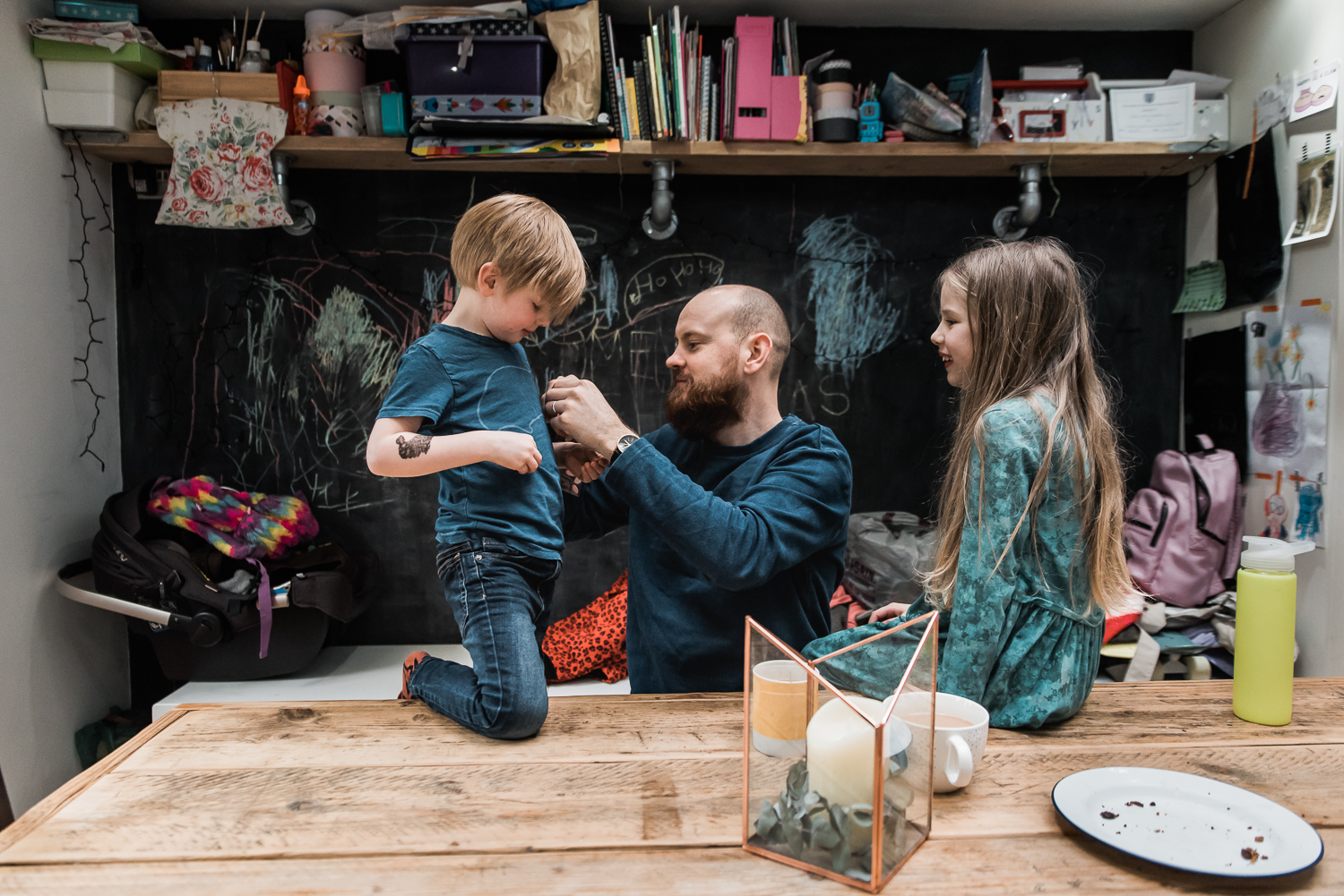 daughter, son, dad at the kitchen table colourful room