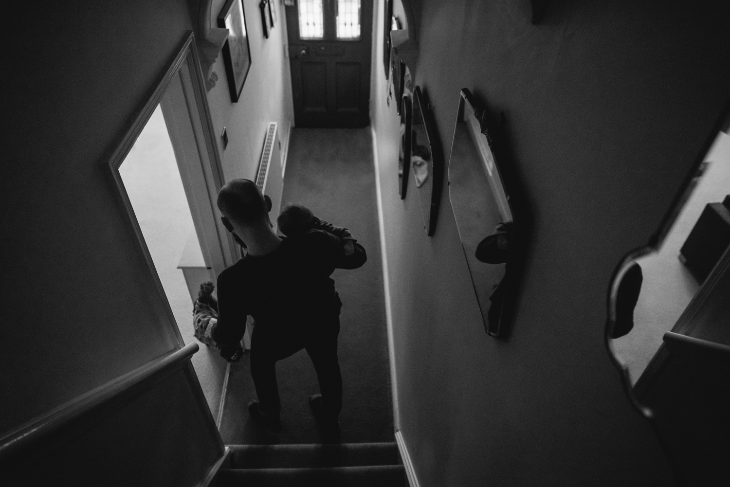 father goes downstairs with baby quiet mood black and white