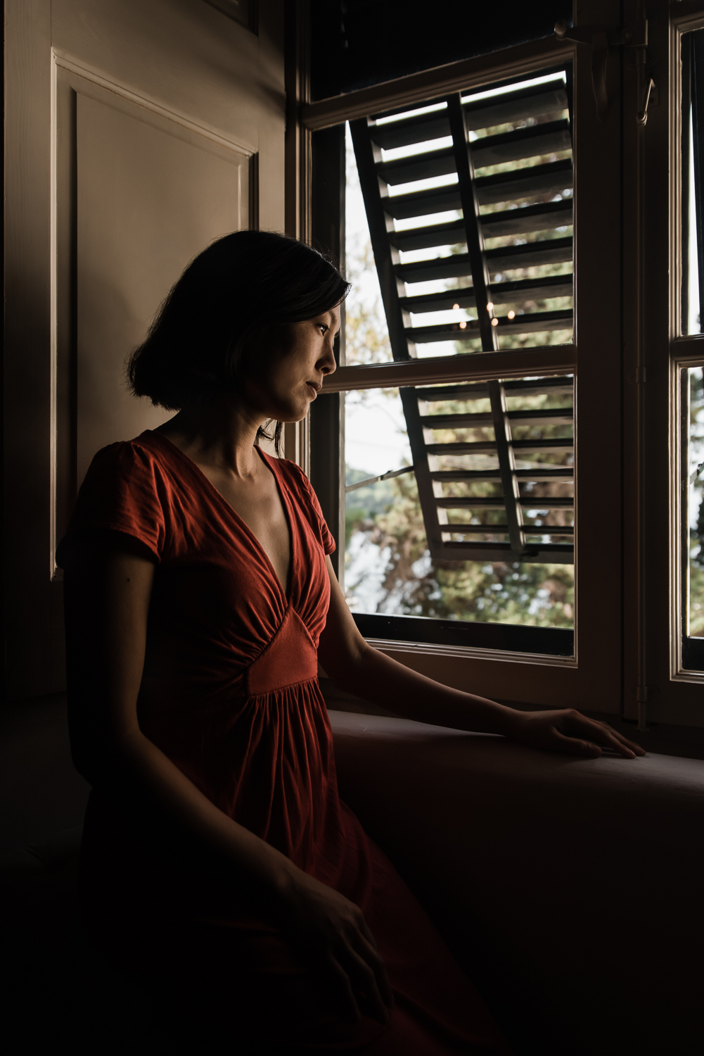 woman in red dress sitting by the window for dear photographer magazine