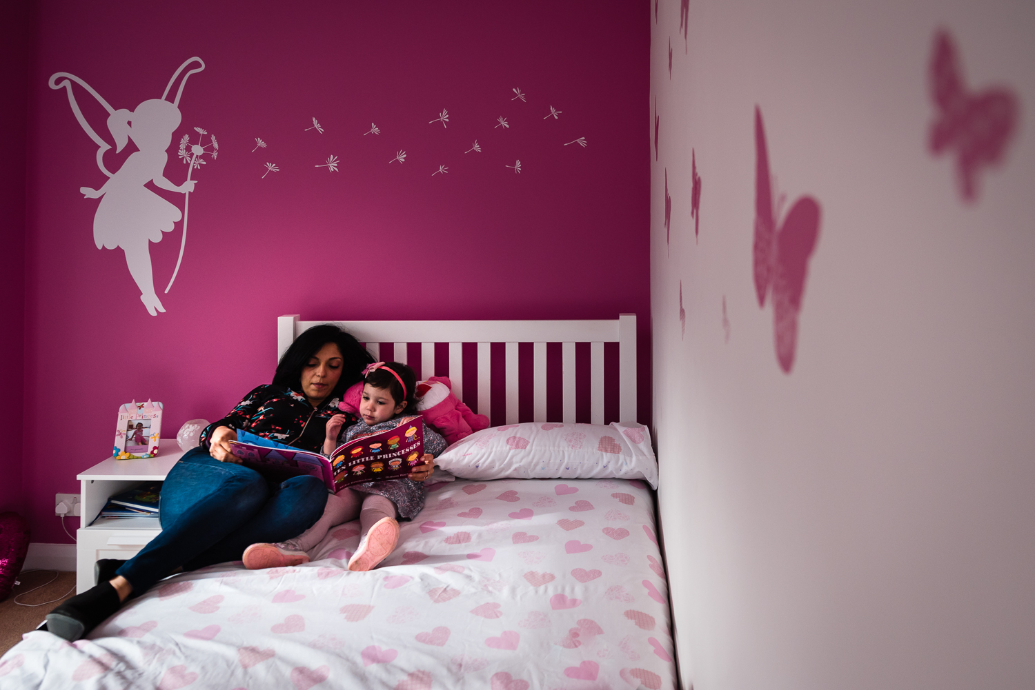 mother reading to child in bed pink walls lifestyle documentary