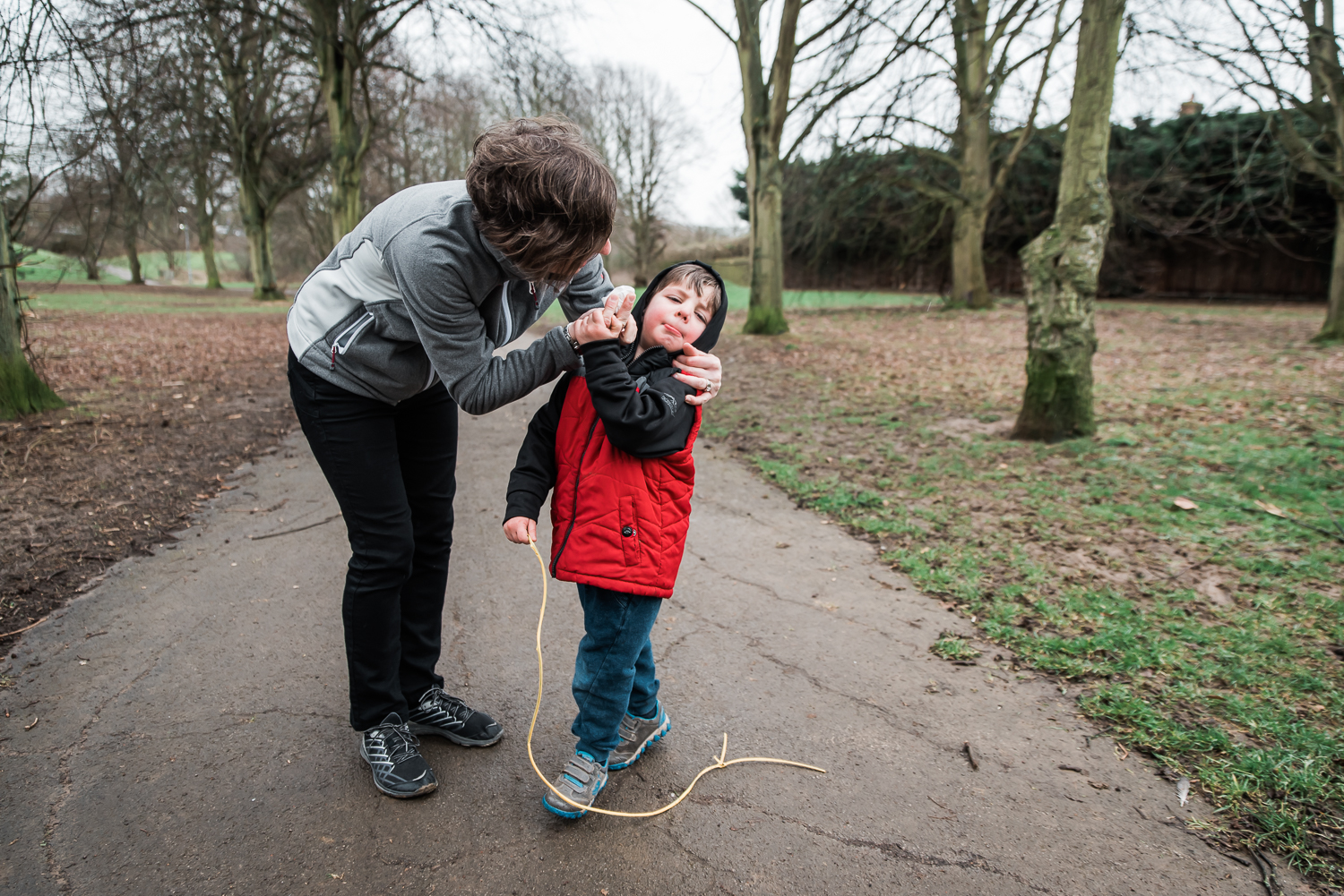 Copy of Mother wiping her boys nose in the park
