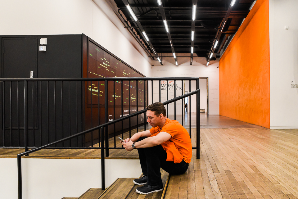 Man sitting on steps texting orange top and wall in the backgrou