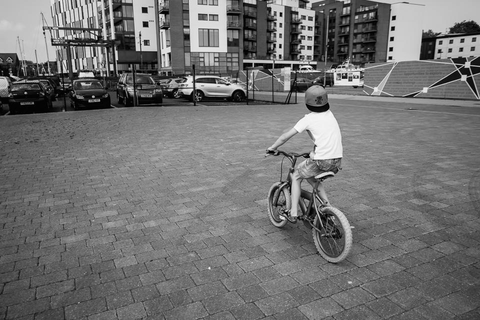 Boy on his bike with a backward baseball cap in black and white