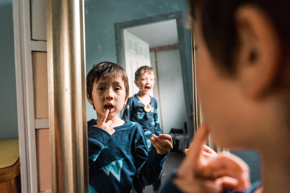 Boy looks at his reflection in the mirror