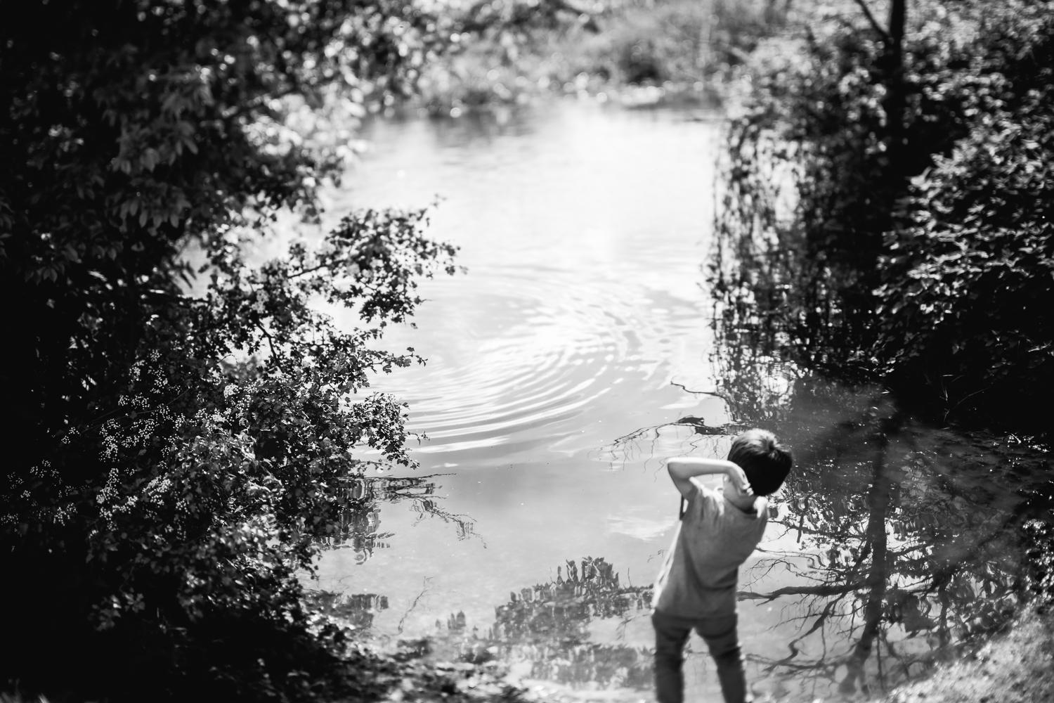Child throwing stones in a river black and white photograph