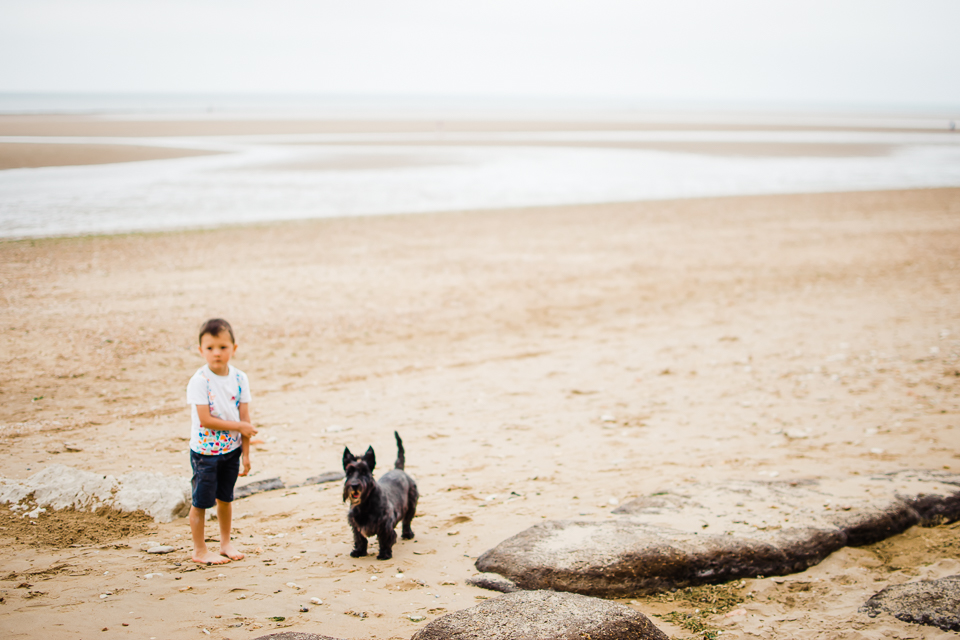Freelensed portrait of young boy and his dog on the beach on the