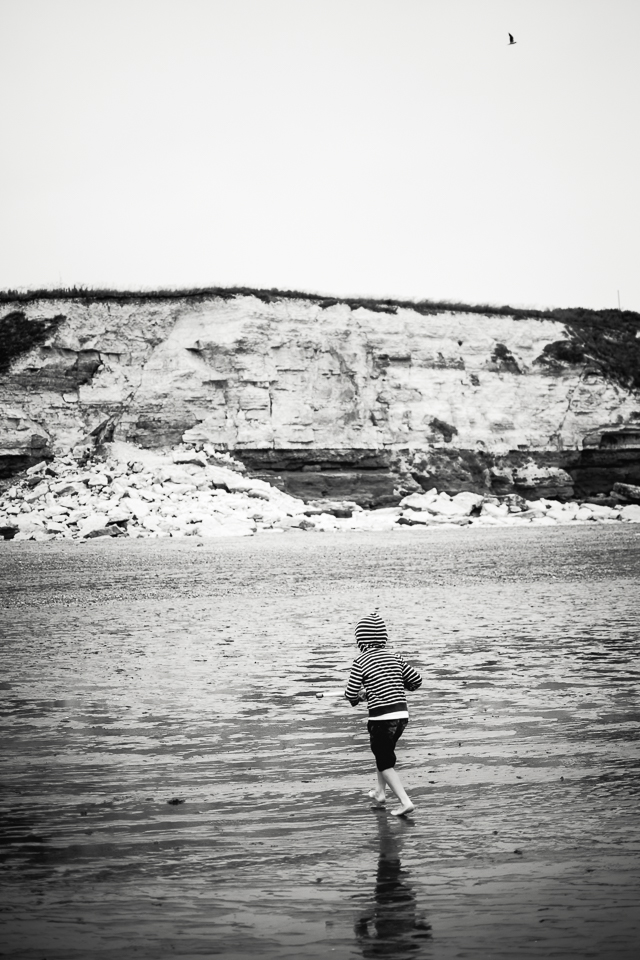Black and white photograph of Hunstanton cliffs with boy on the