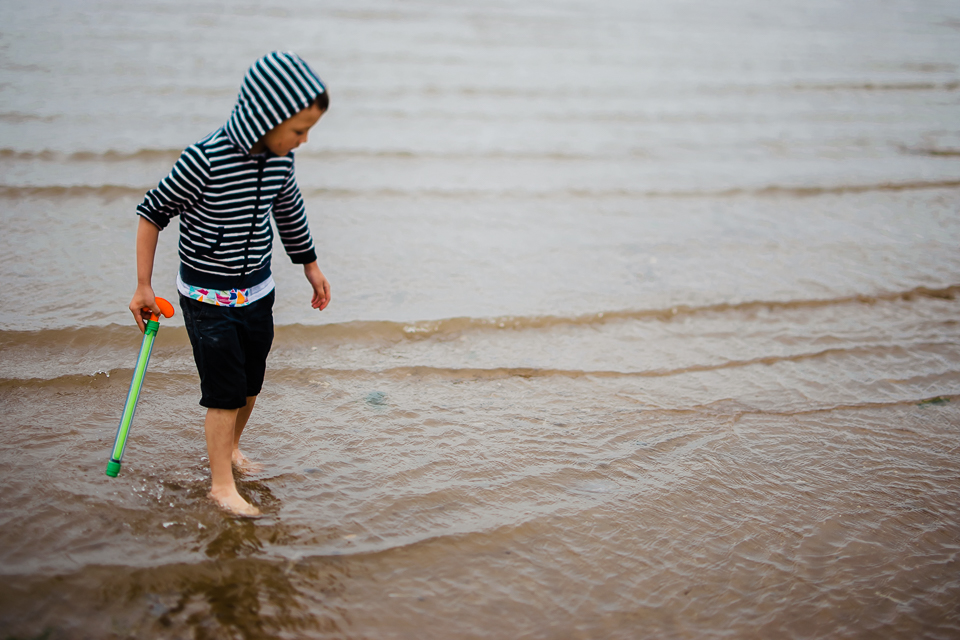 Boy on the beach looking at jellyfish washed out to sea