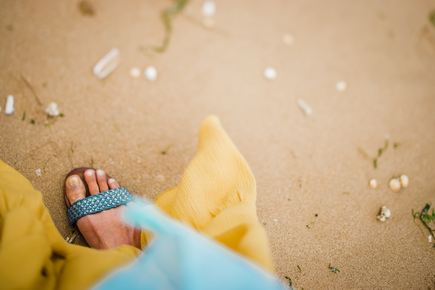 Stepping onto the sand at Hunstanton beach in yellow dress and b