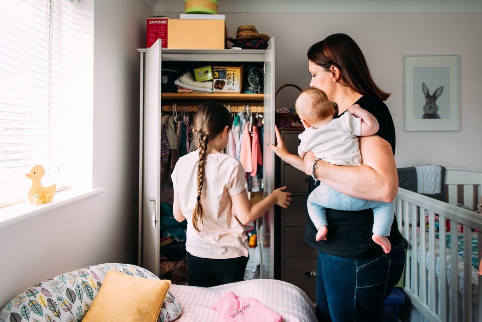 Mother and daughter choosing baby clothes in the bedroom