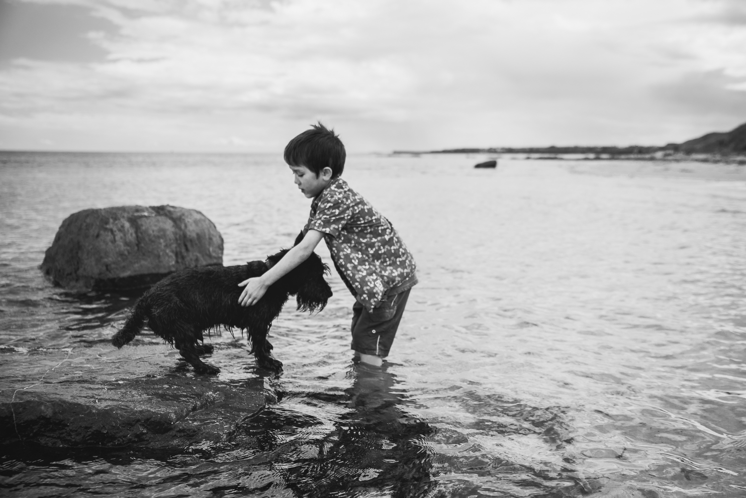 Black and white photograph of a boy and his dog in the sea
