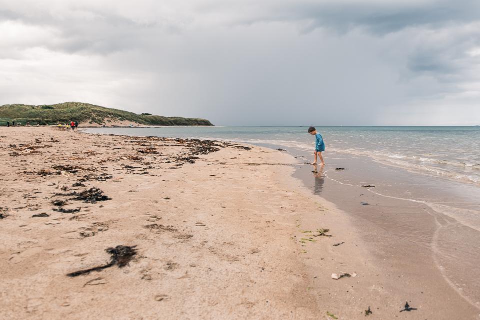Child walking on the beach at Bamburgh