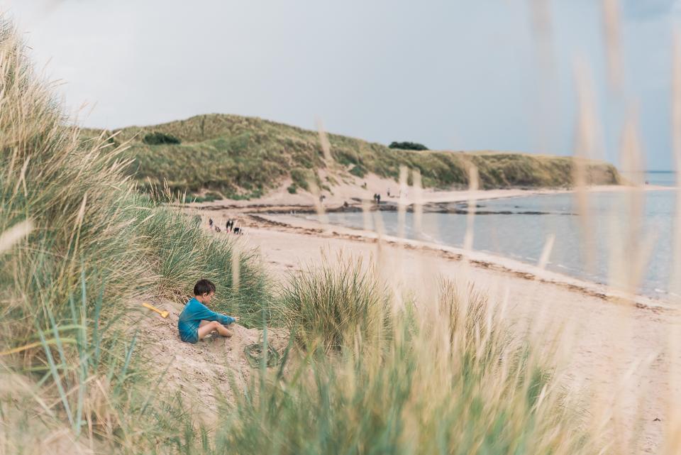 Child on the sand dune at Bamburgh beach