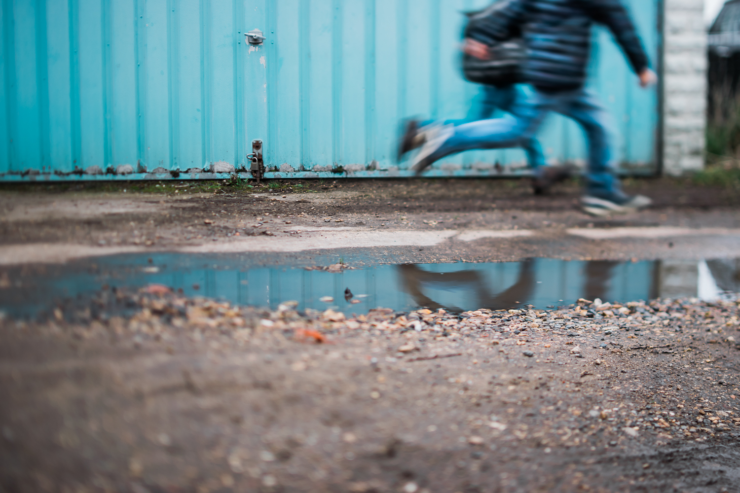 Freelensed photograph of boys running and their reflection blue