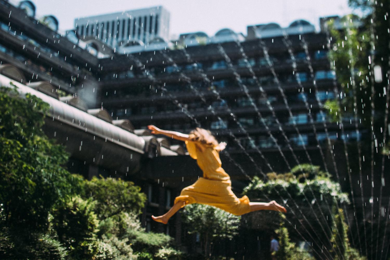Model Sam Payne jumps through sprinklers at the Barbican