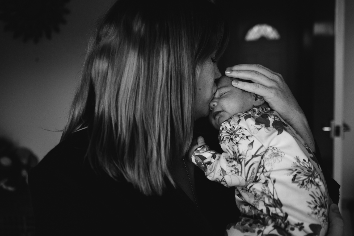 Black and white photograph of a mum kissing her baby's forehead
