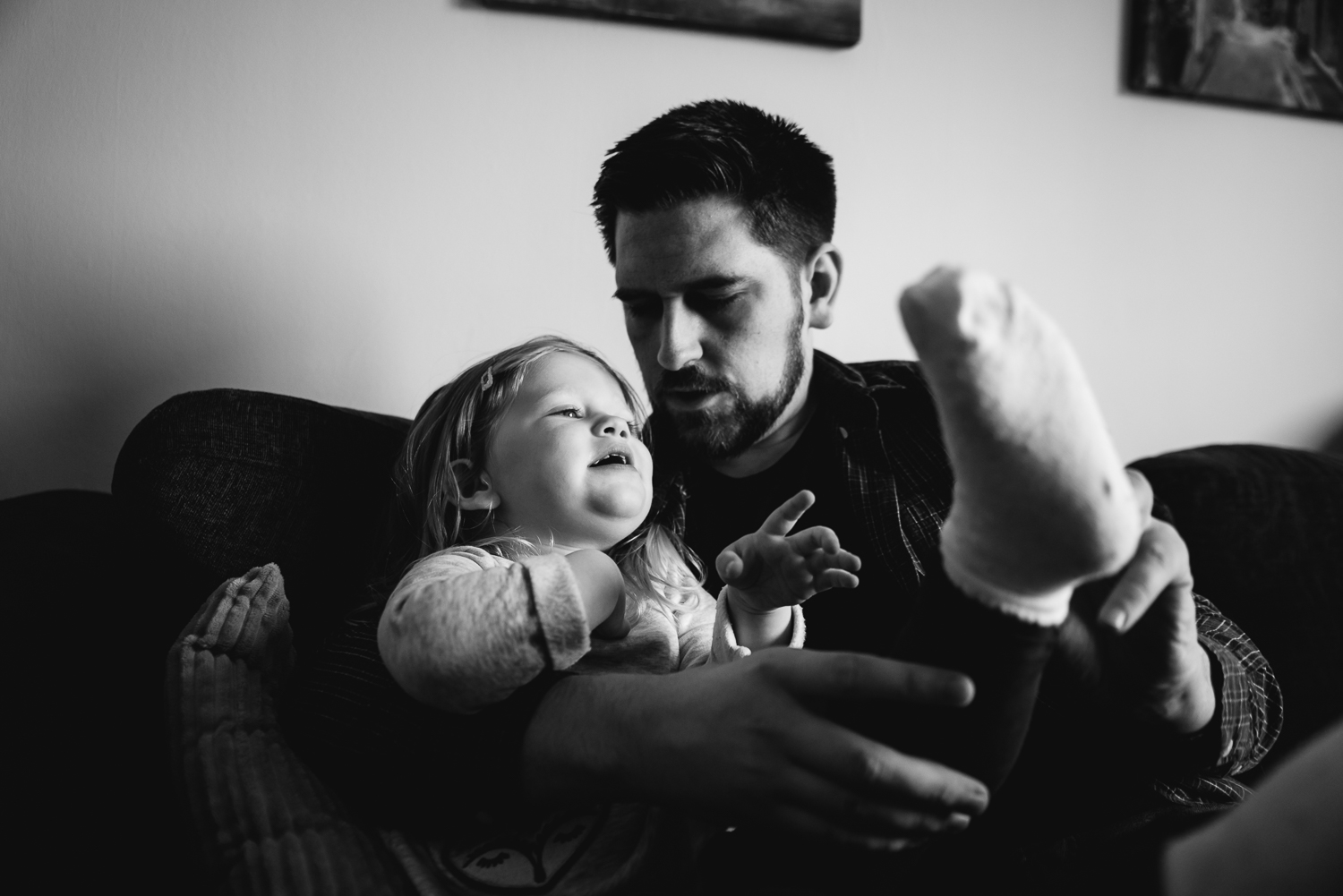 Black and white photograph of father putting sock on his daughte