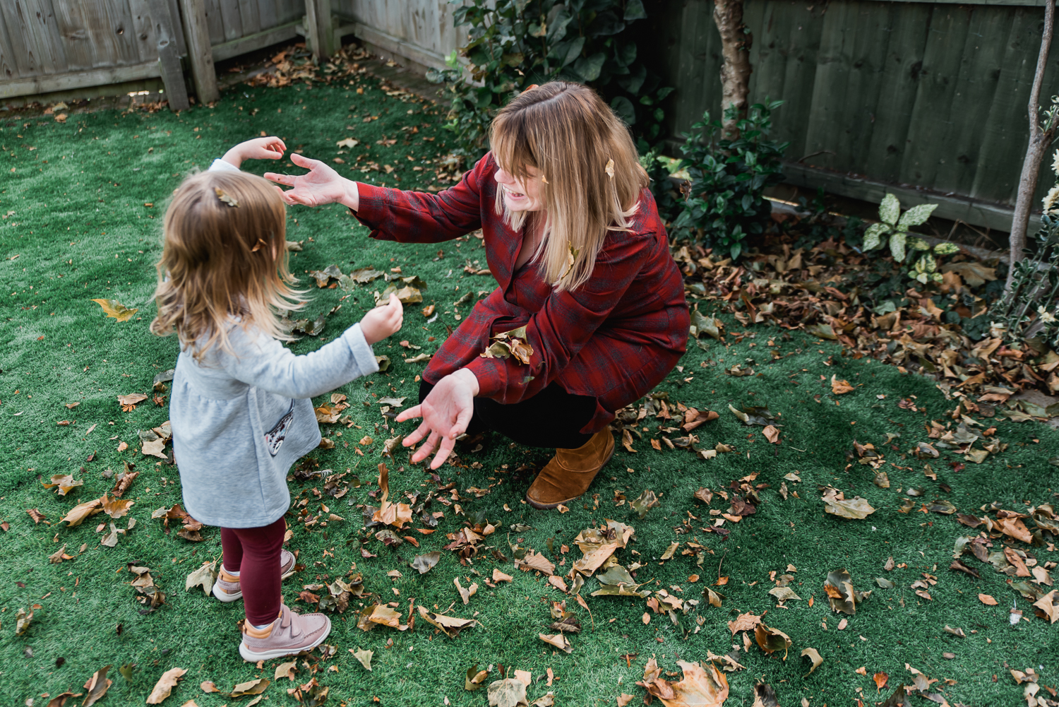 Mum and daughter dressed in red playing with the brown leaves in