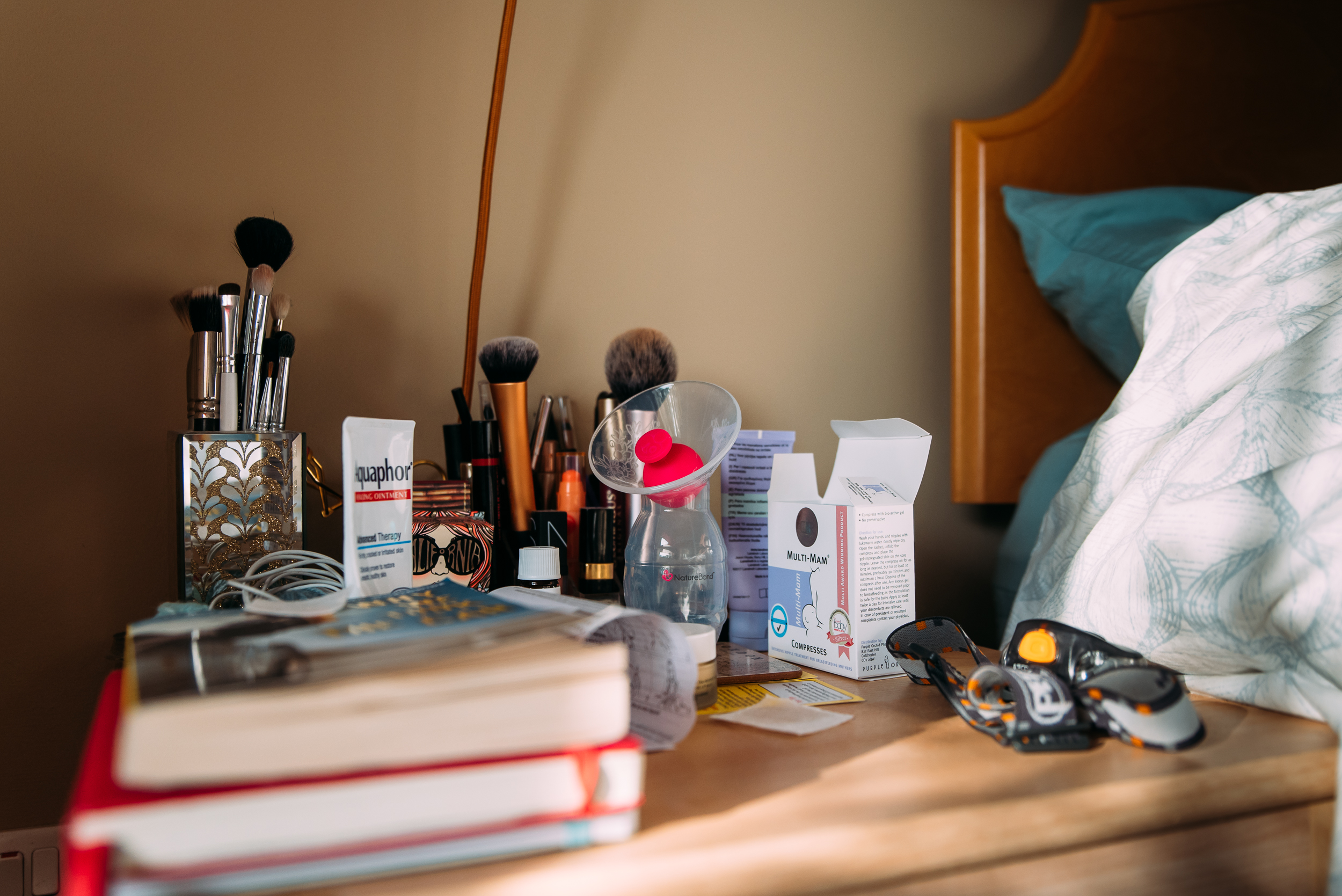 Make up brushes and breast milk container lies by the side of th