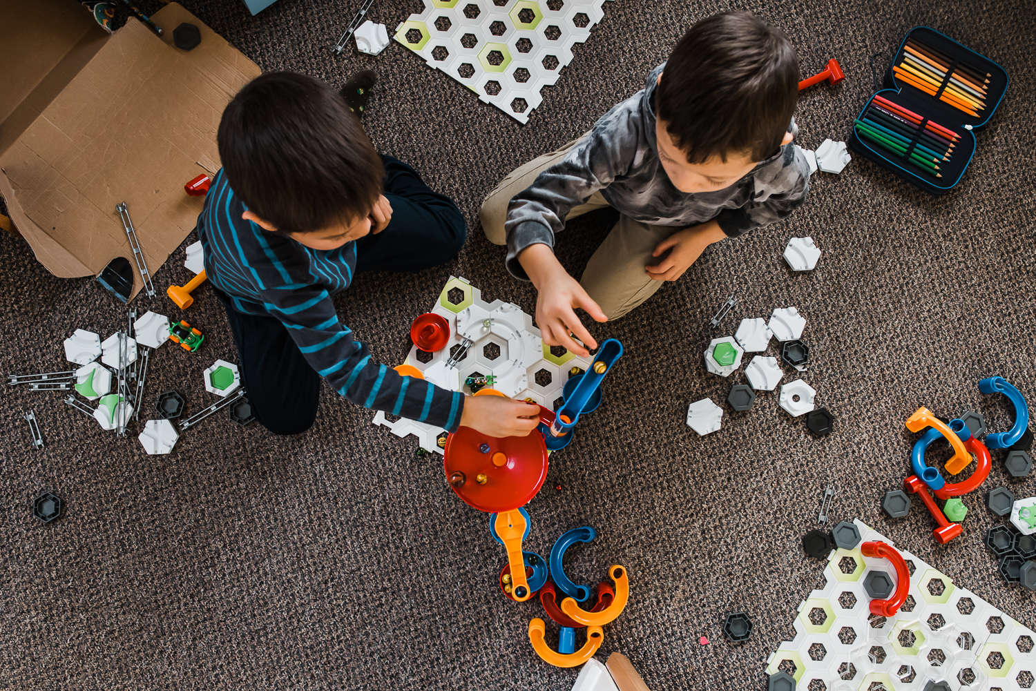 Two brothers playing with their marble track creation.
