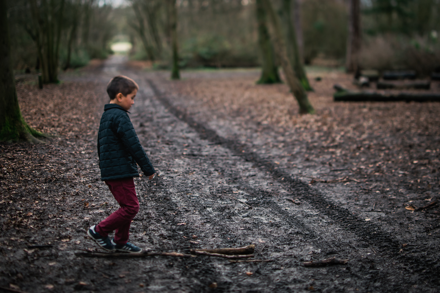 Boy walking across a muddy track in Hinchingbrooke Park, Hunting