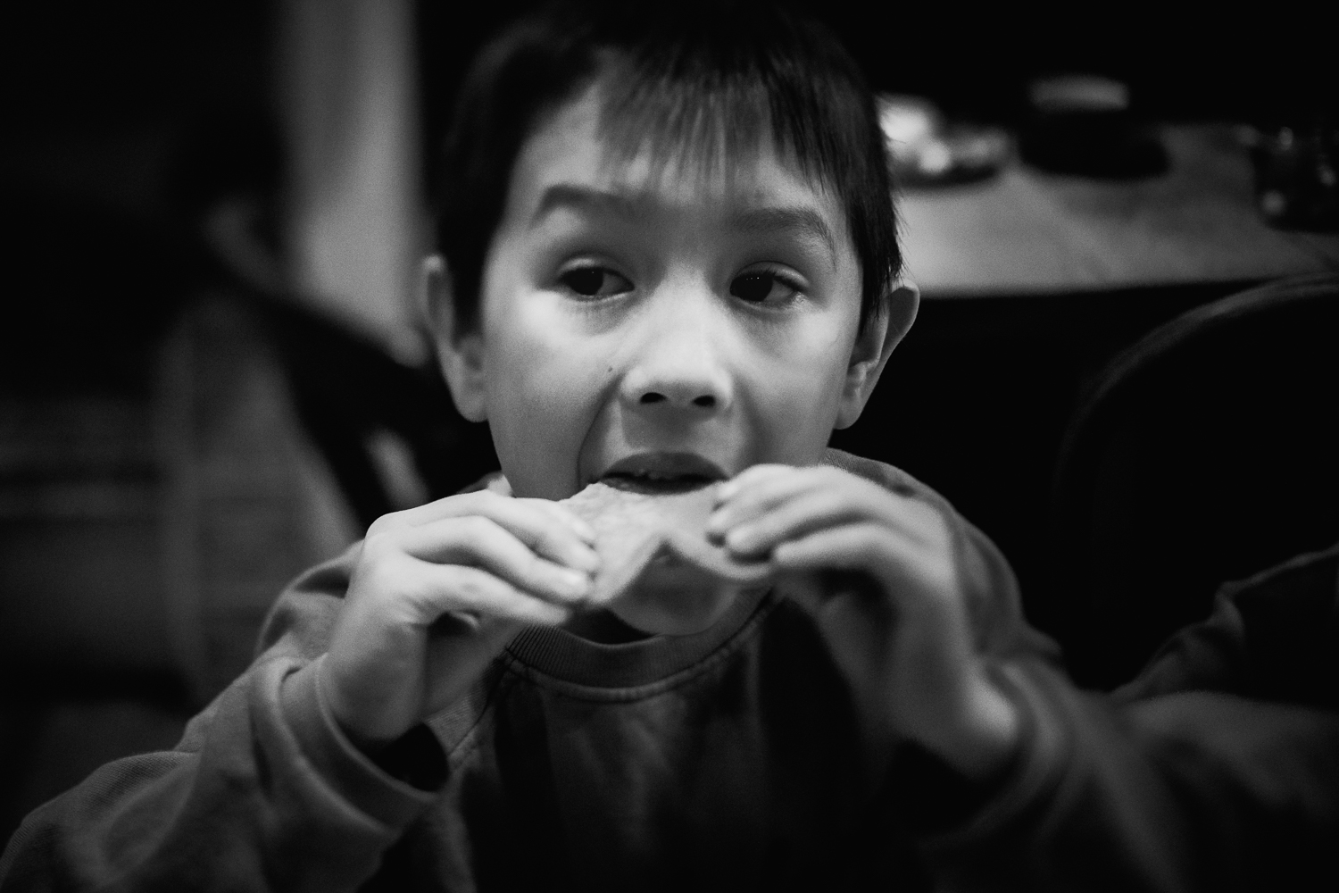 Boy biting into a gingerbread biscuit