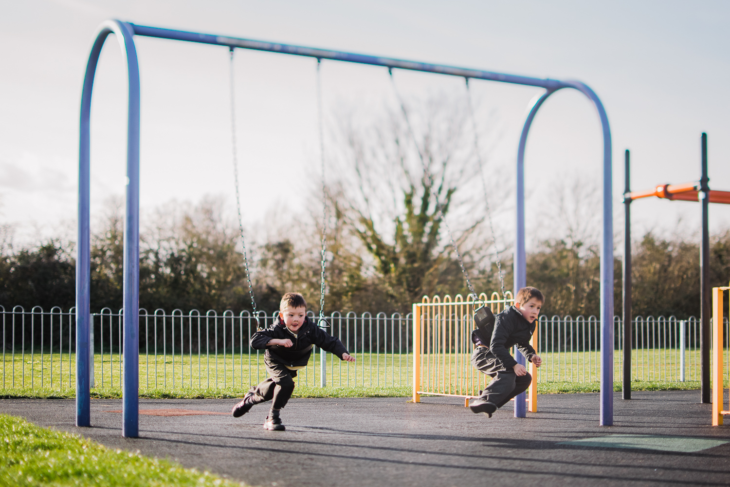 Two children on the swings in the playground, Huntingdon, Cambri