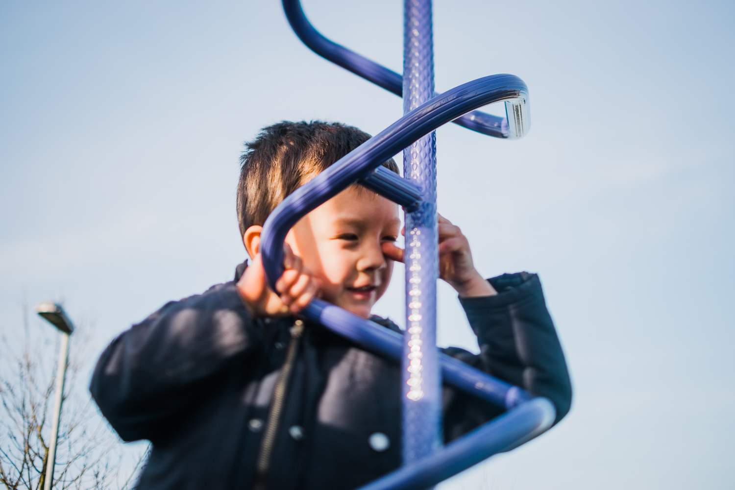 A child on the lookout on the playground pole equipment