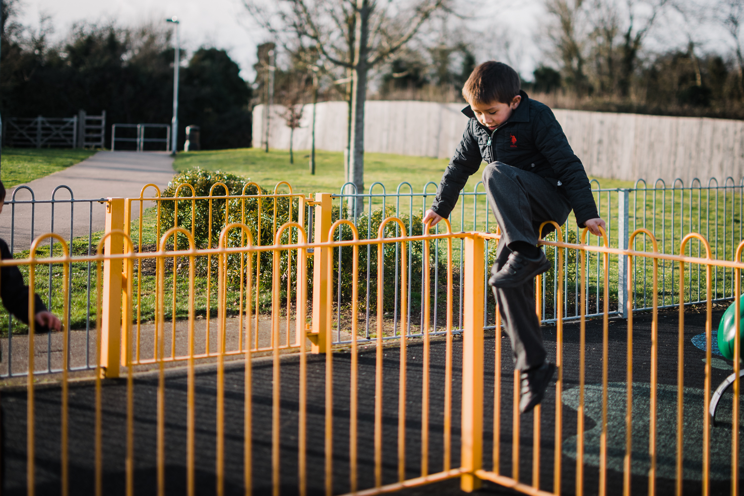 A boy climbs over a yellow railing in the playground