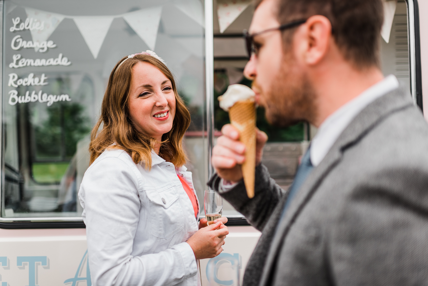 Male guest eating ice-cream while a woman watches on at a festiv