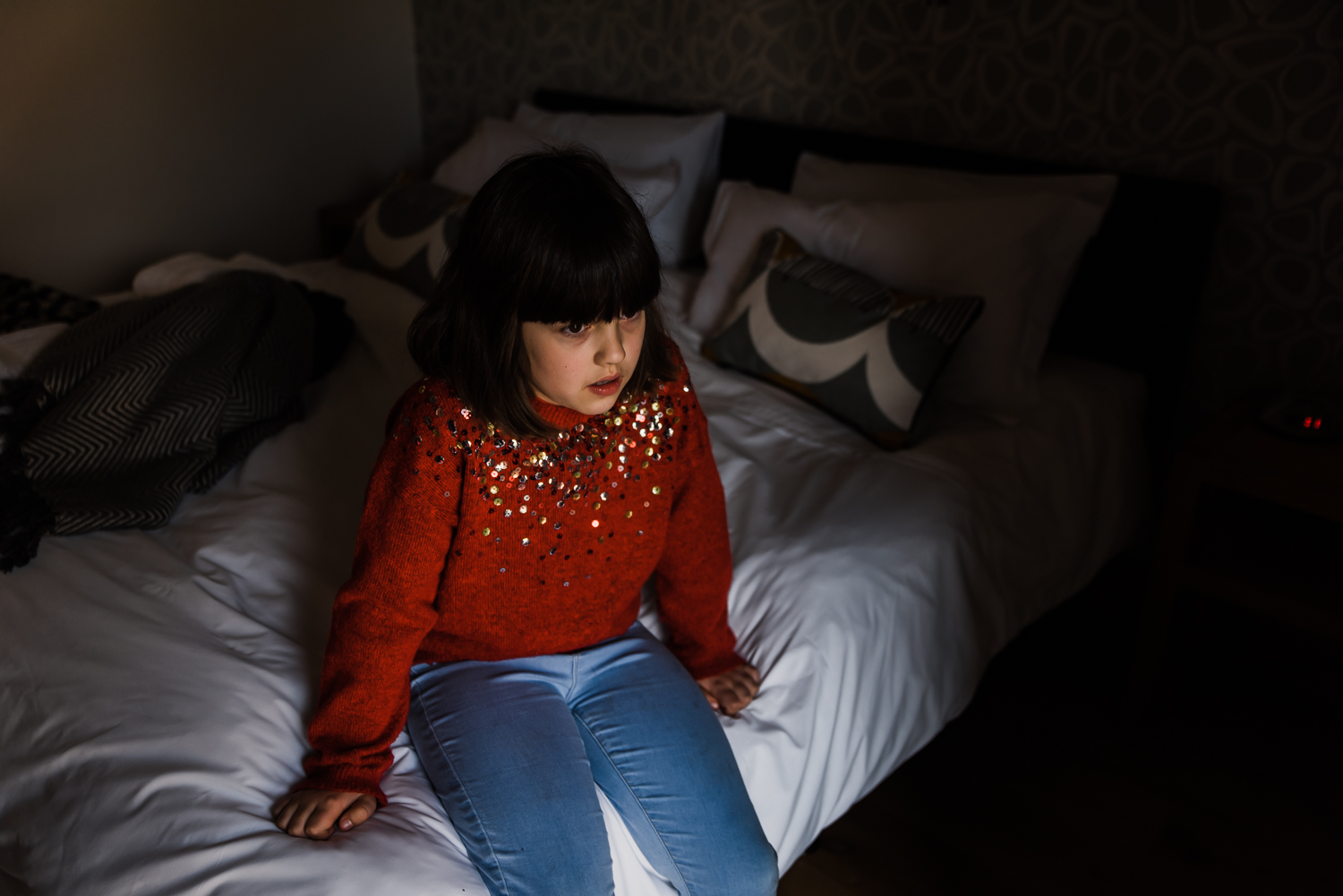Girl in a red sequin jumper sitting on a bed in a child portrait