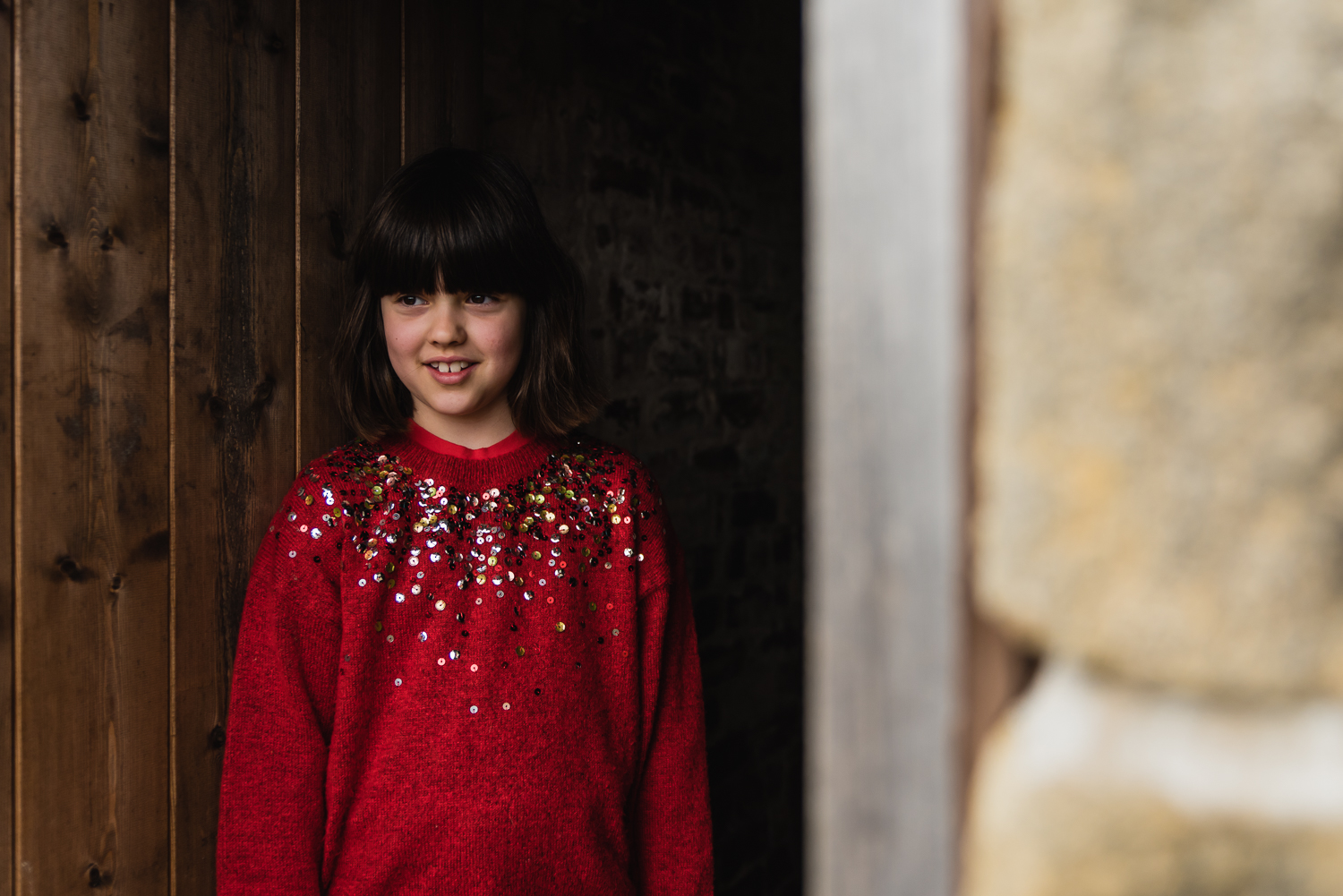 Girl in a red sequin jumper framed in a doorway at a child portr