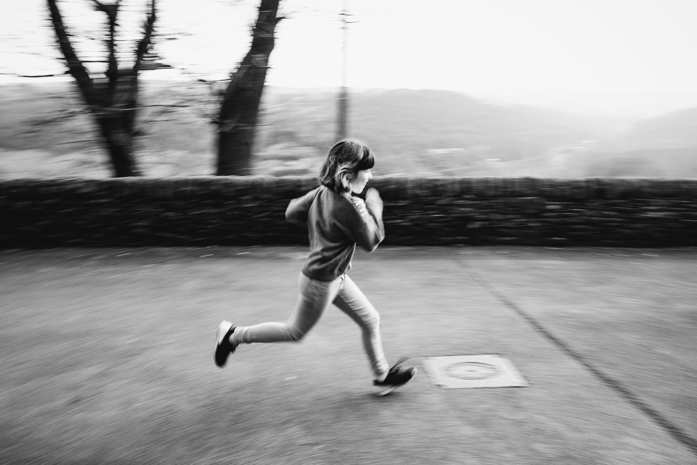 Black and white panning photo of child running