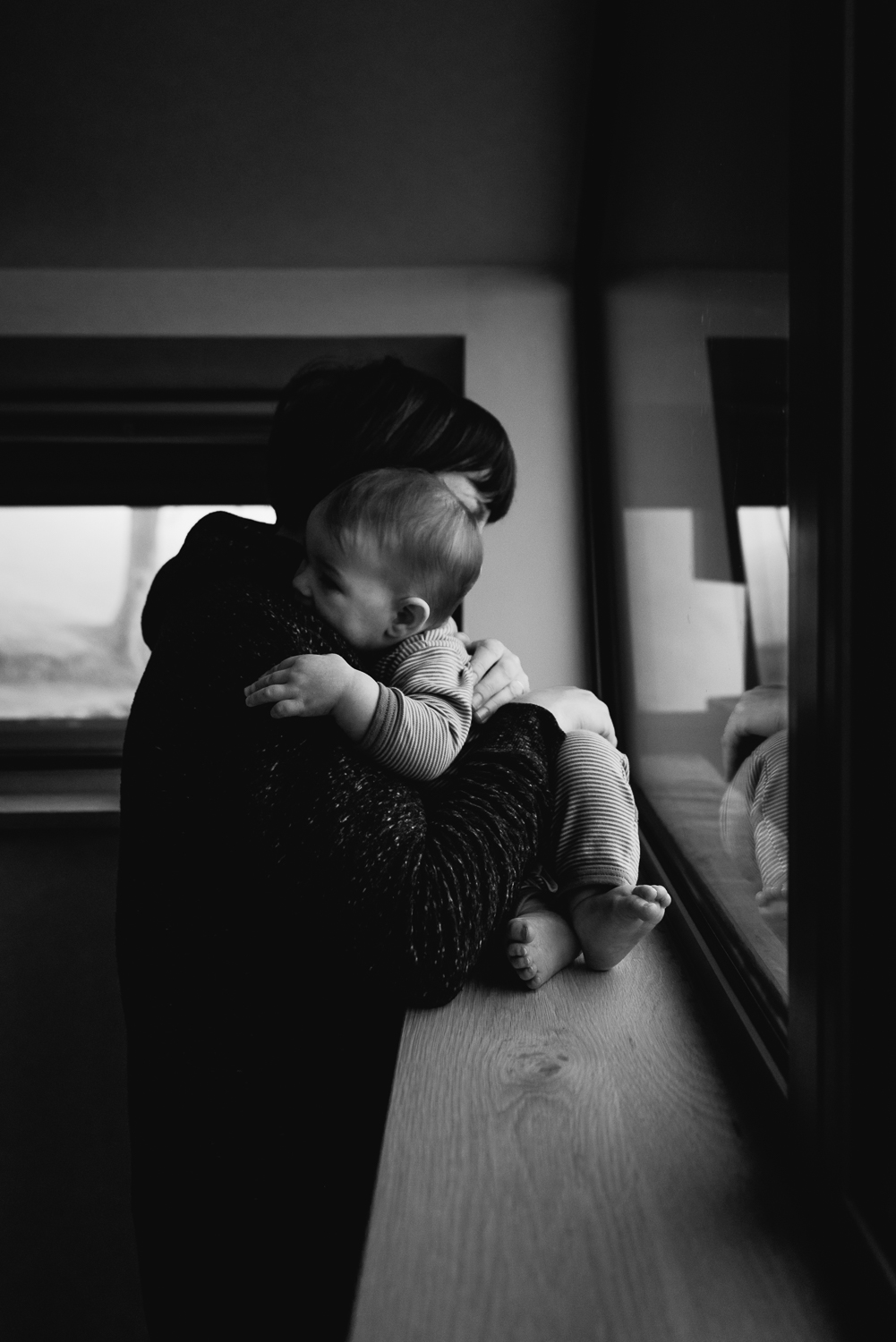 Black and white documentary photograph of a mother cuddling her