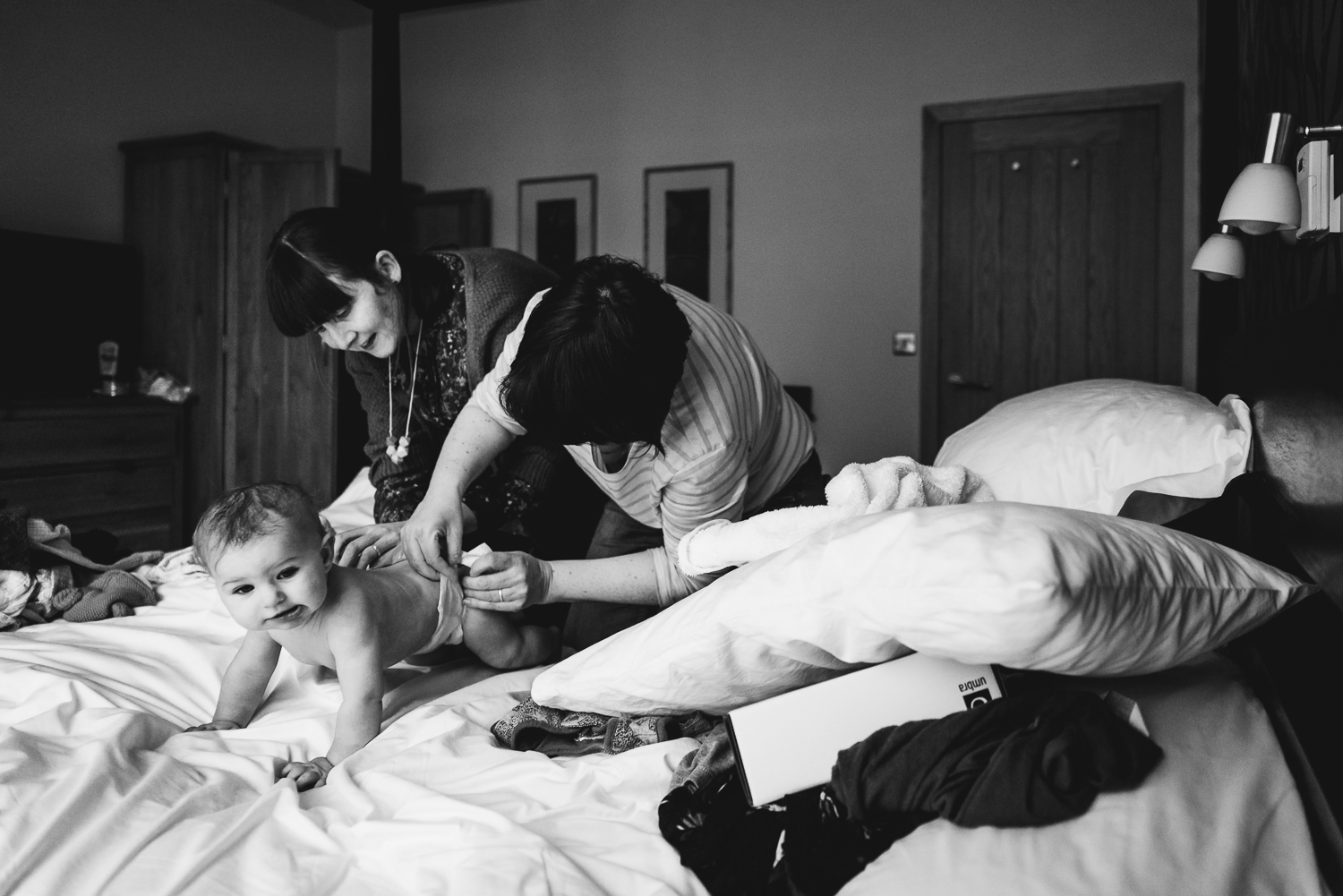 Black and white photograph of two mothers dressing their baby fo