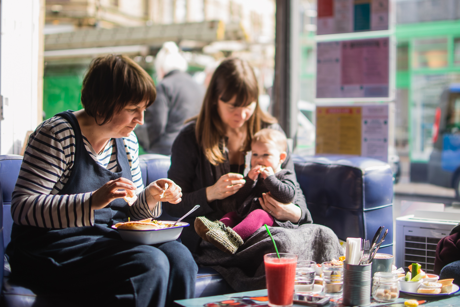 Two mothers and their baby eating out in a cafe during a day-in-