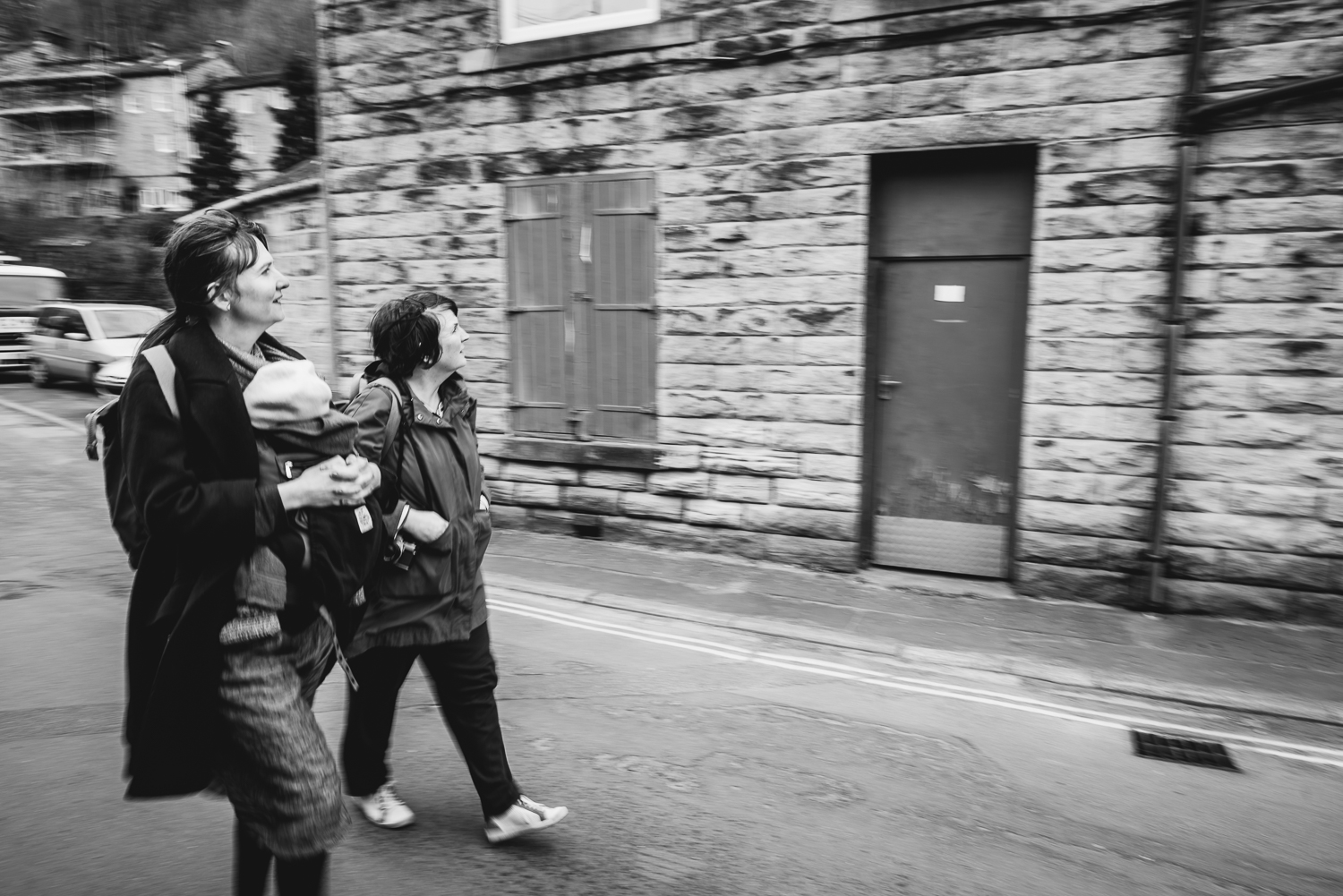 Black and white photography of a family walking past an old buil