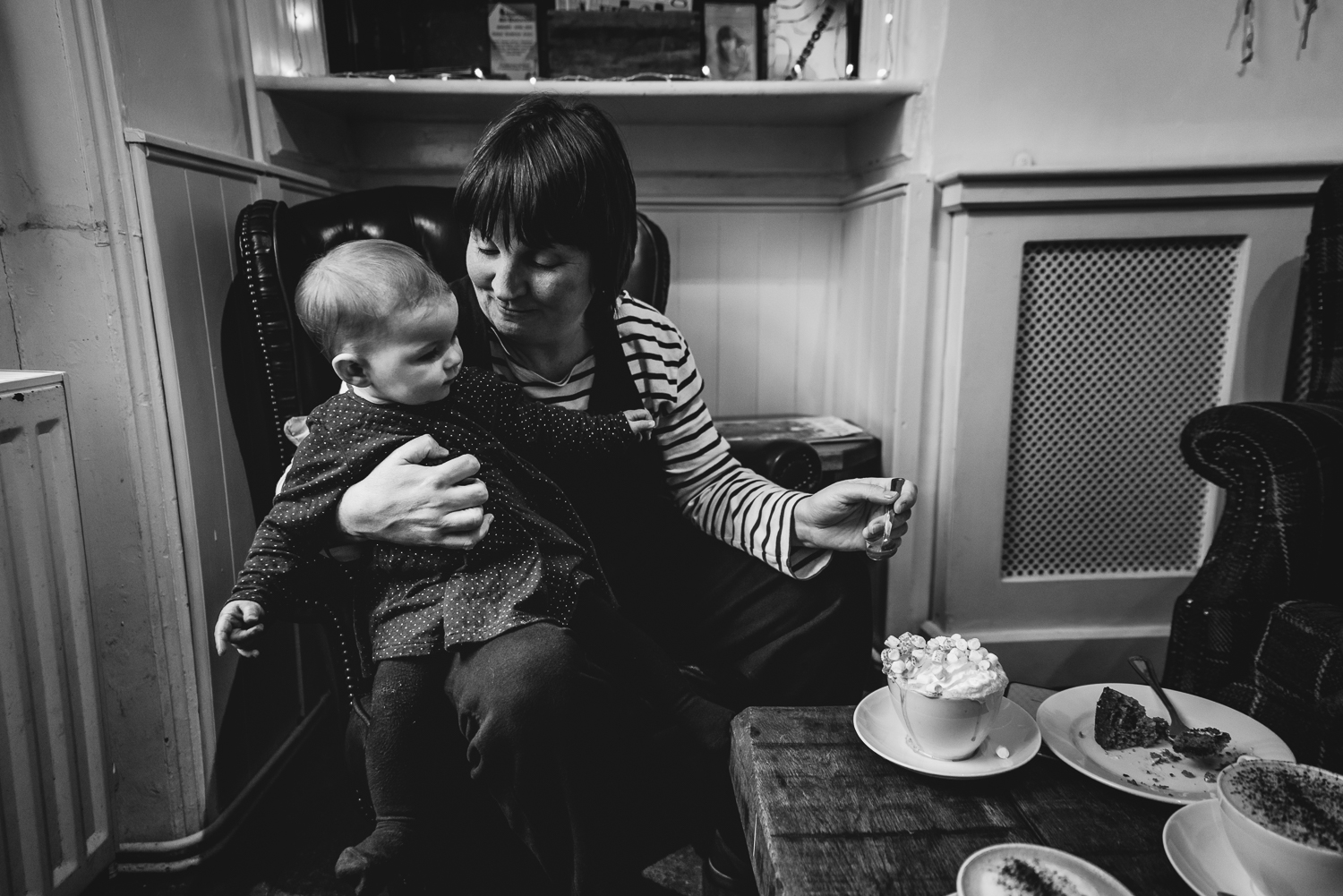 A black and white photograph of a mother and her child at a cafe