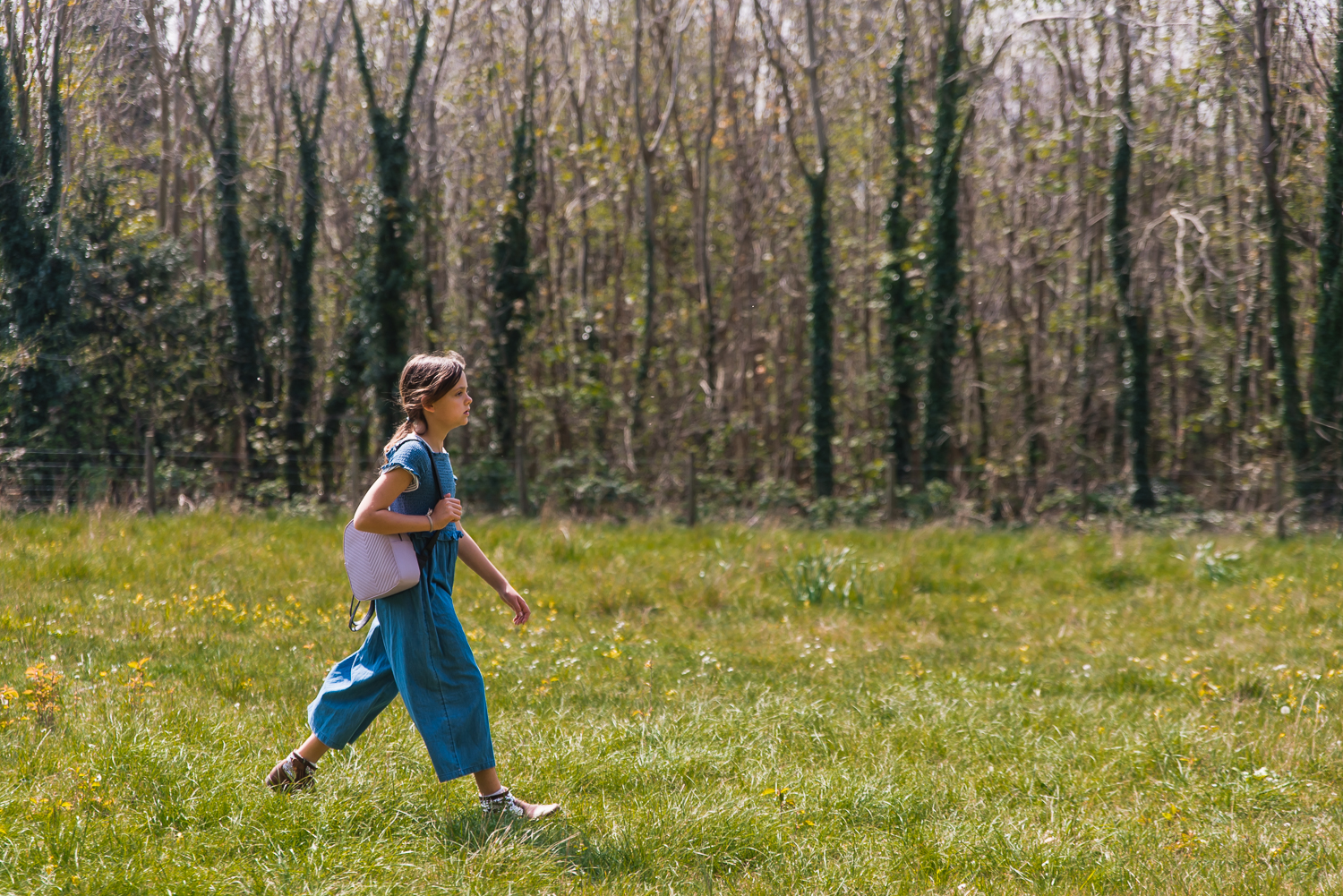 Girl carrying her pink rucksack walking across a field