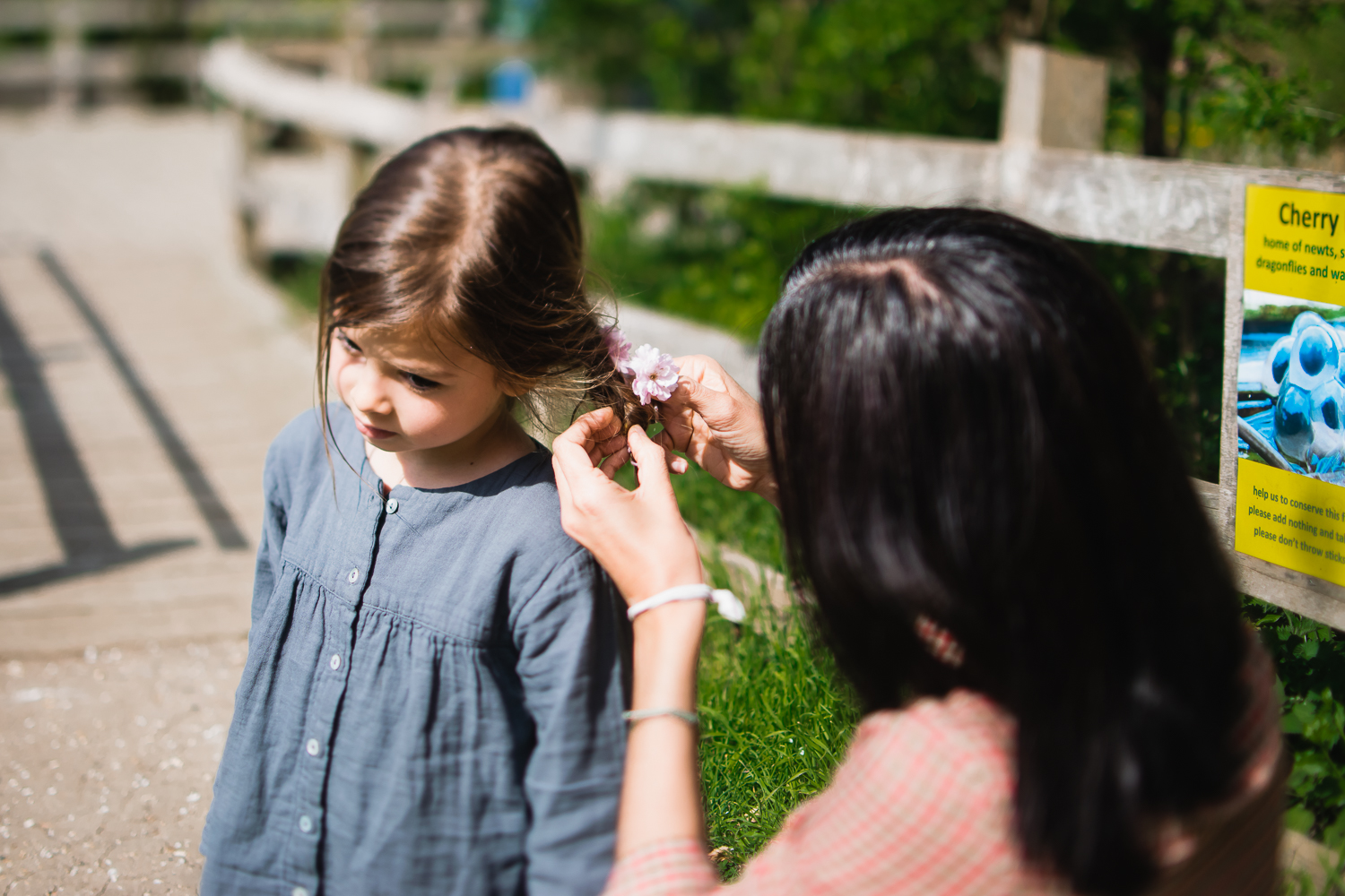A mum putting a pink flower in her daughter's hair