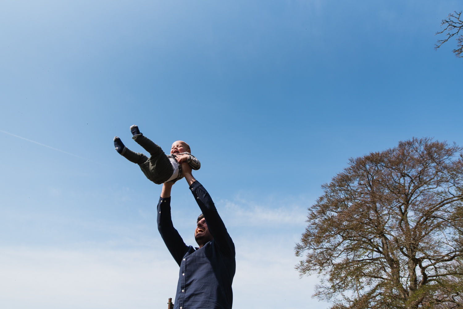 A father swinging his baby in the air on a family photoshoot with Diana Hagues Photography