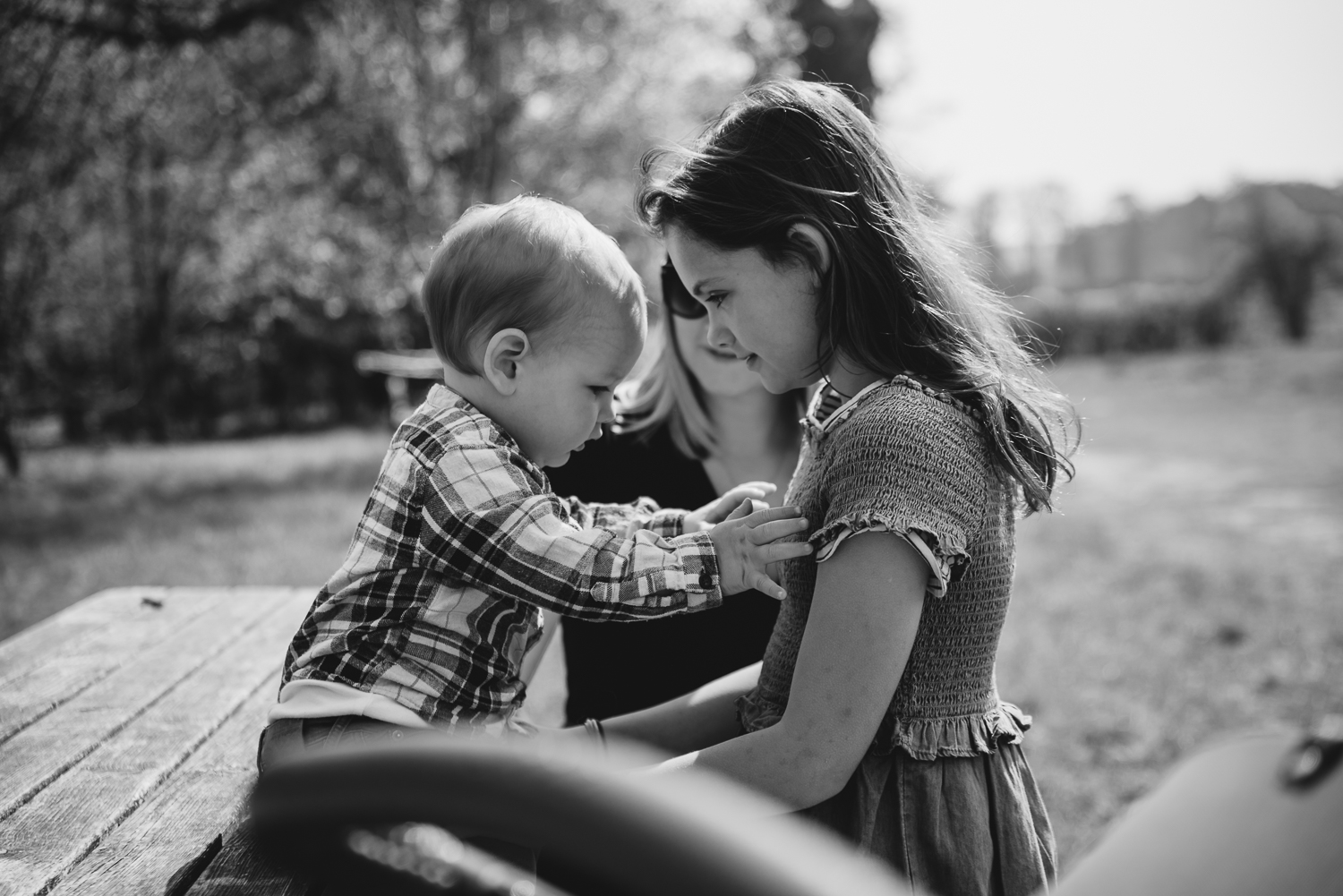 A baby reaching out to cling onto his cousin in a family photography session in Cambridge