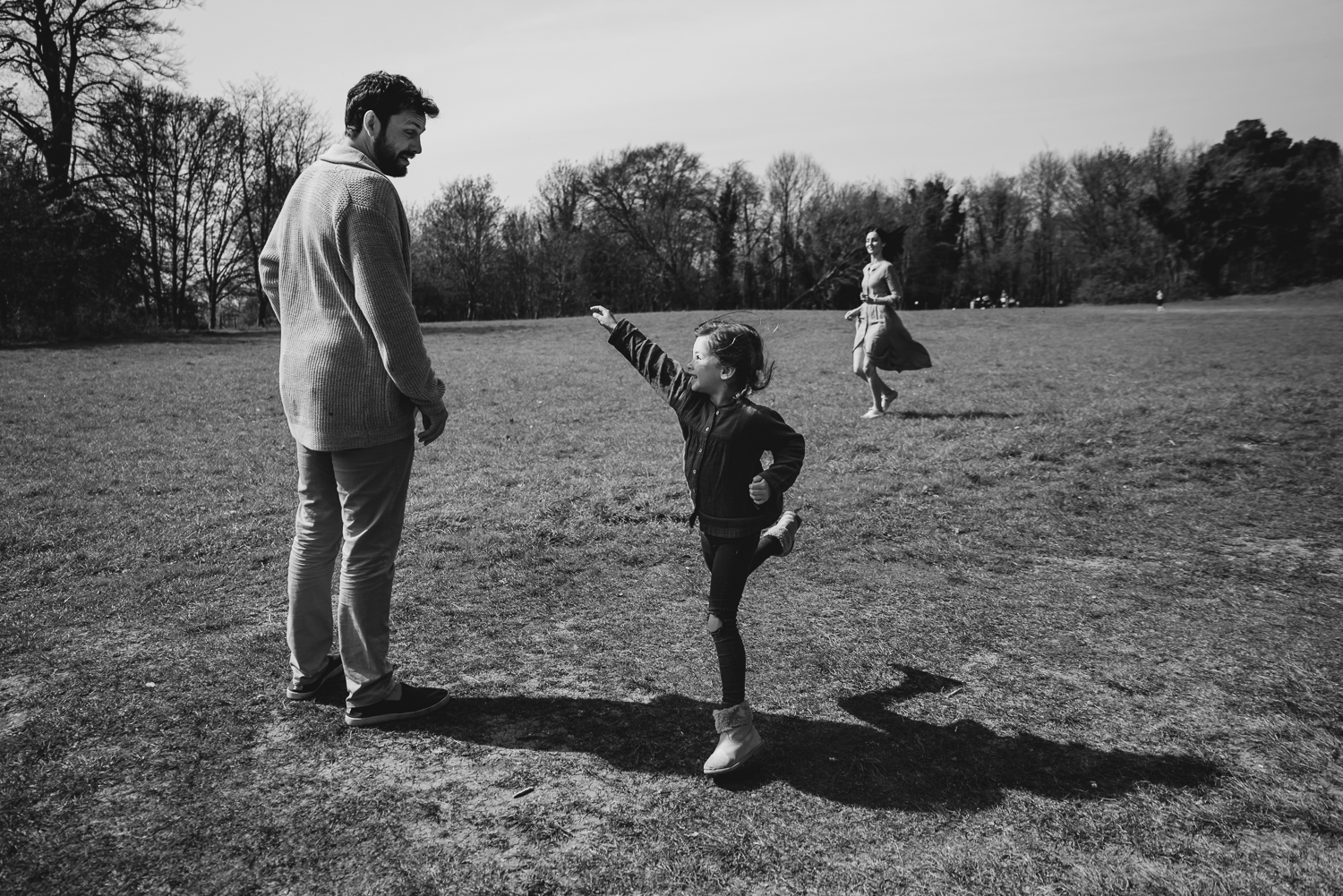 Black and white photograph of a mum and dad running around in a field and their daughter leaping into the air.