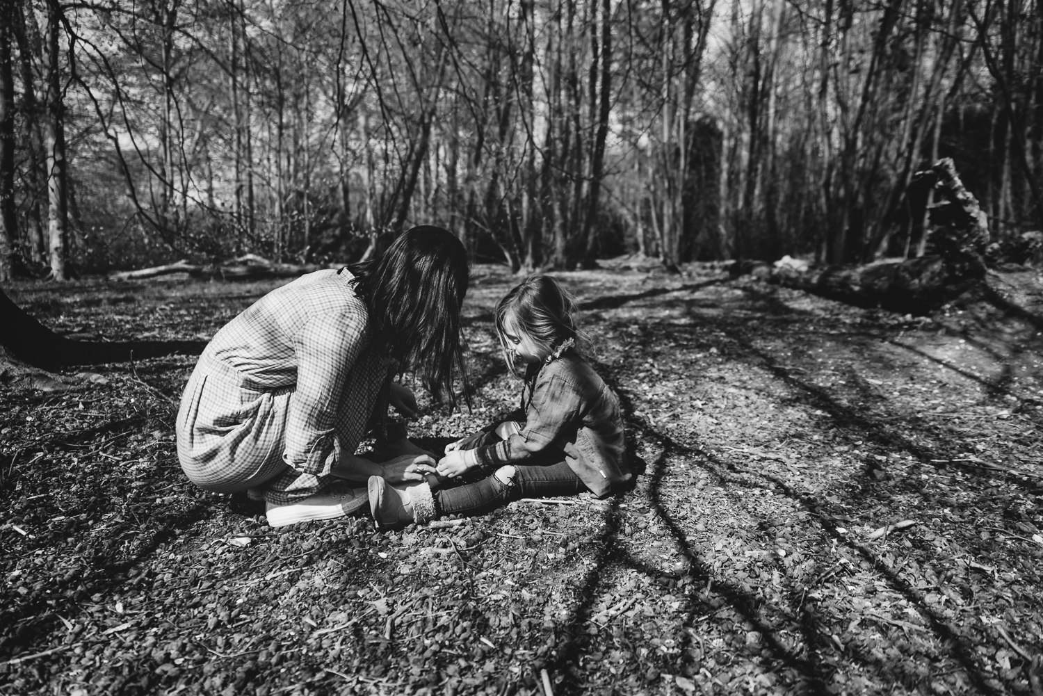 Black and white photograph of a mum tending to her daughter whilst sitting on the ground in strong tree shadows